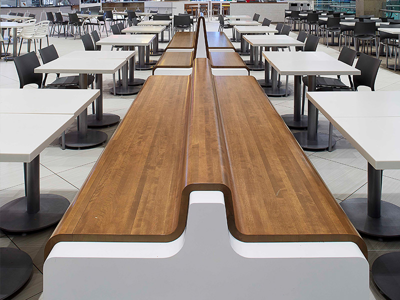 The banquette seating with its molded wood and corian structure is backless, making it a strong departure from typical food court seating.