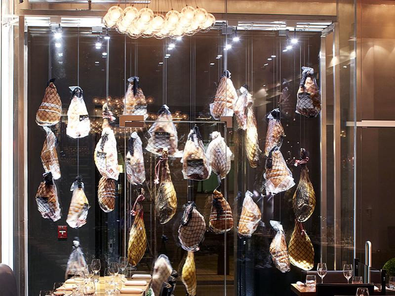 Le  jambon qui dans un présentoir vitré éclairé avec raffinement souligne avec humour la place qu'occupe le cochon dans l'établissement.